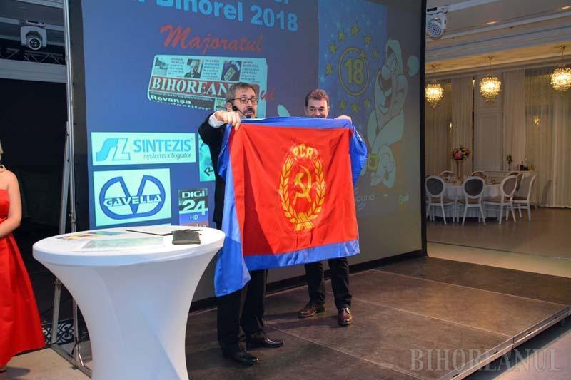 CU DOUĂ FEŢE. În lipsă, europarlamentarul Emilian Pavel a primit cadou un steag cu două feţe: pe-o parte este cel al Uniunii Europene, de unde PSD-istul îşi ia salariul de multe mii de euro, iar de cealaltă parte drapelul Partidului Comunist Român, care pare să-i ghideze pe social-democraţi în activitatea din ţară
