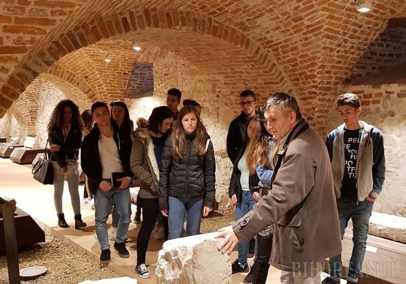 """TOTUL ÎN GHIDAJ. Săptămâna trecută, reporterul BIHOREANULUI s-a intersectat în Lapidariul Cetăţii Oradiei cu un grup de studenţi ghidaţi de muzeograful Dumitru Noane (în prim plan). Nu acelaşi noroc îl au vizitatorii pe cont propriu, condamnaţi să afle doar cât le """"spun"""" lapidarele etichete din dreptul exponatelor, pentru că Muzeul Cetăţii nu are niciun sistem de tip audio-ghid"""