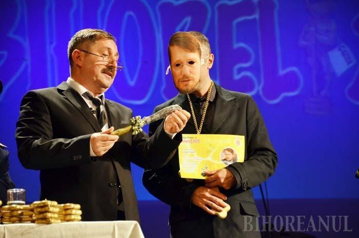"""CU MASCĂ, FĂRĂ MASCĂ. Drept """"pedeapsă"""" că a refuzat invitaţia BIHOREANULUI, Szabo Odon a primit premiul printr-un personaj mascat: un cuţit numai bun de înfipt în spate şefului său de partid"""