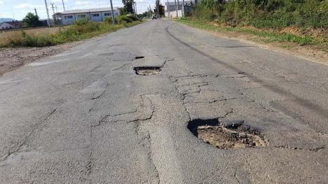 Strada nimănui: Un drum plin cu gropi, pasat de la Primăria Beiuș la CJ, îi scoate pe șoferi din sărite
