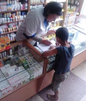 Desculţ, sărac lipit, dar disperat să înveţe carte: Povestea copilului care-şi face lecţiile cu o farmacistă, pe tejghea