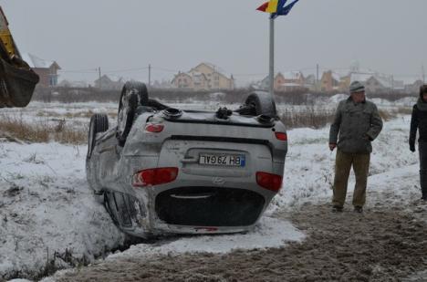 Se circulă greu pe şoselele din Bihor: În Sânmartin, o maşină s-a întors cu roţile-n sus (FOTO)