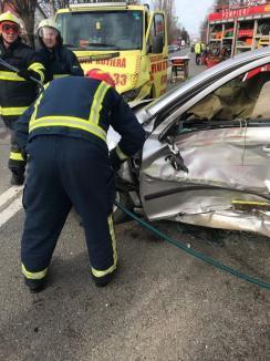 Accident între un autoturism și o mașină cu platformă pe Calea Clujului din Oradea: O persoană a rămas încarcerată (FOTO)