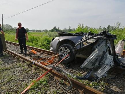 O maşină s-a izbit de tren lângă Finiş şi a fost târâtă 100 de metri. Un bărbat, în stop cardio-respirator (FOTO / VIDEO)
