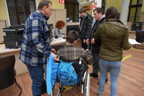Umilitor! Orădeni cu dizabilităţi locomotorii, căraţi pe braţe de angajaţii Primăriei, ca să depună o petiţie (FOTO / VIDEO)