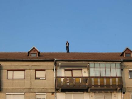 Un tânăr de 20 de ani s-a urcat pe acoperişul blocului şi a aruncat cu butelii, ameninţând că se sinucide