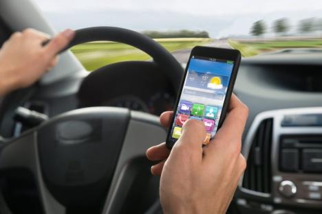 Folosirea telefonului în timpul condusului poate aduce suspendarea permisului